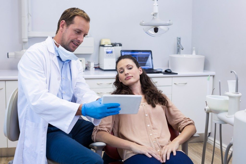 dentist showing patient dental analysis