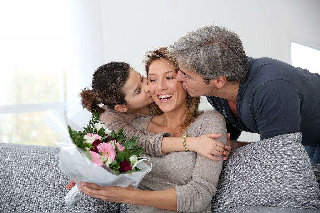 Mom being kissed by her daughter and husband
