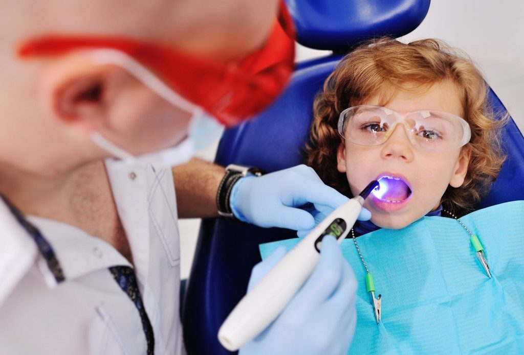 kid getting teeth cleaned by dentist
