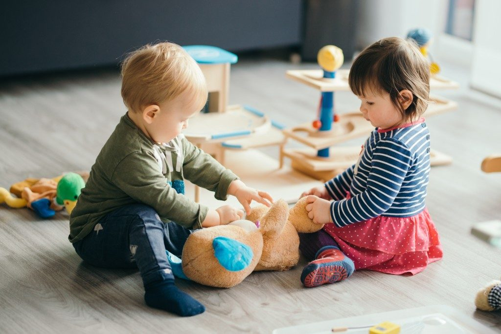 Young boy and young girl playing ball in living room