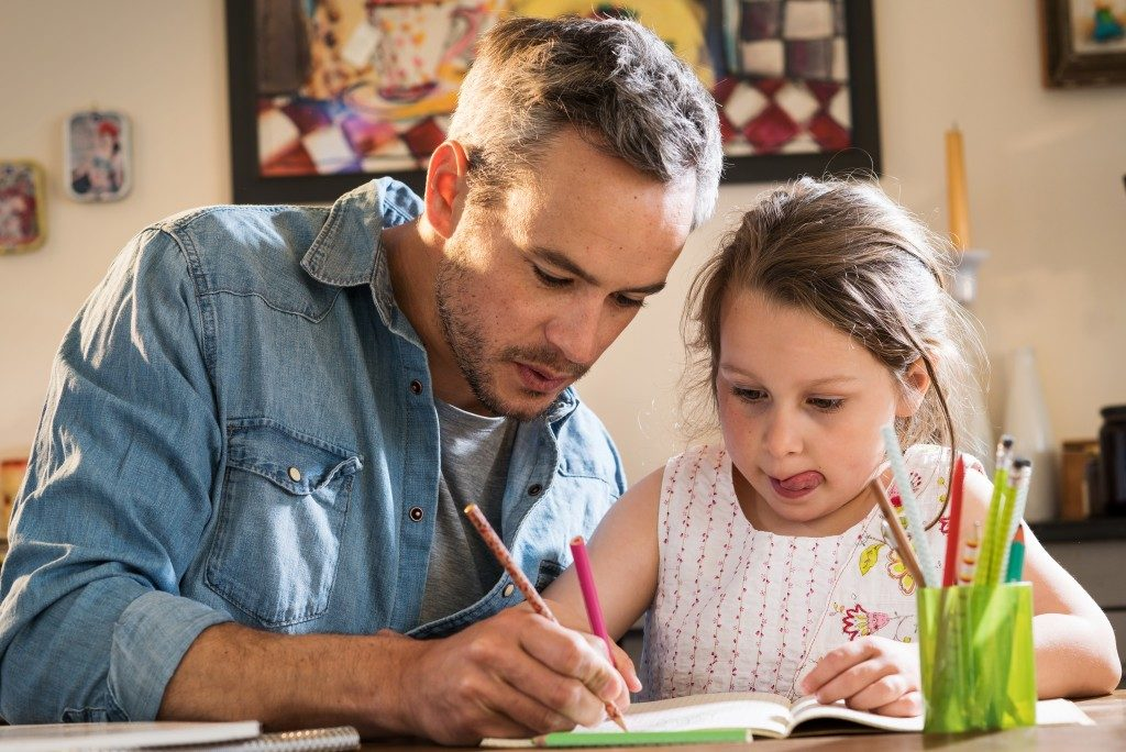 Father helps daughter with homework