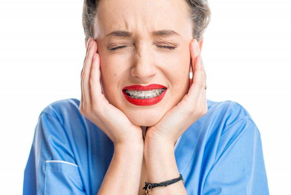 woman in pain wearing braces