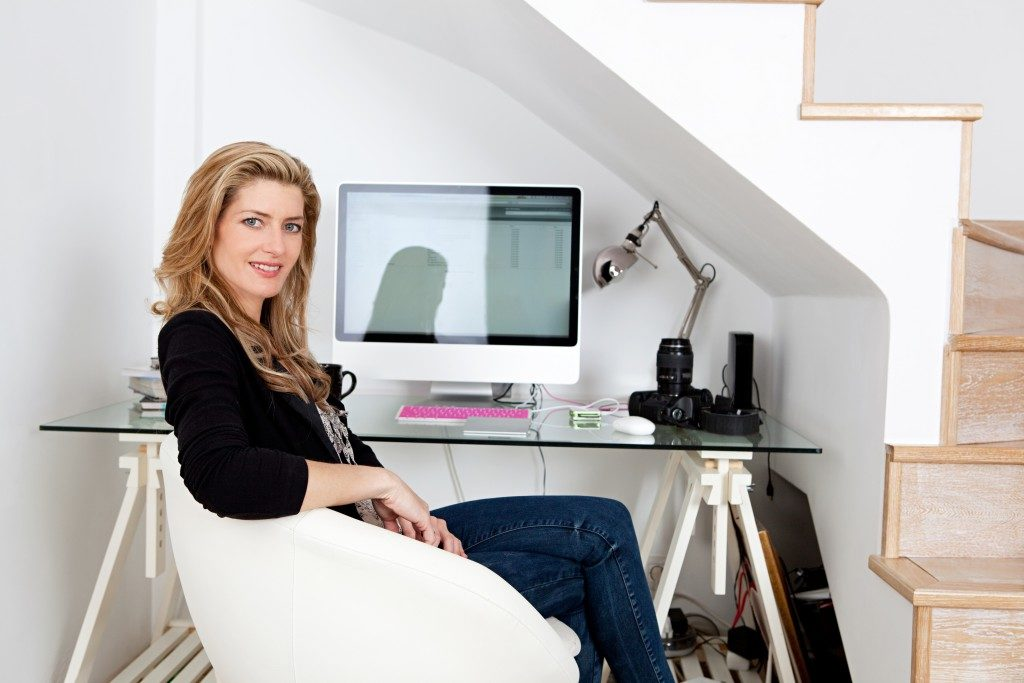 oung professional photographer working from home and sitting at her desk at home