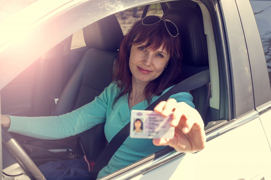 Woman holding out her driver's license while inside the car