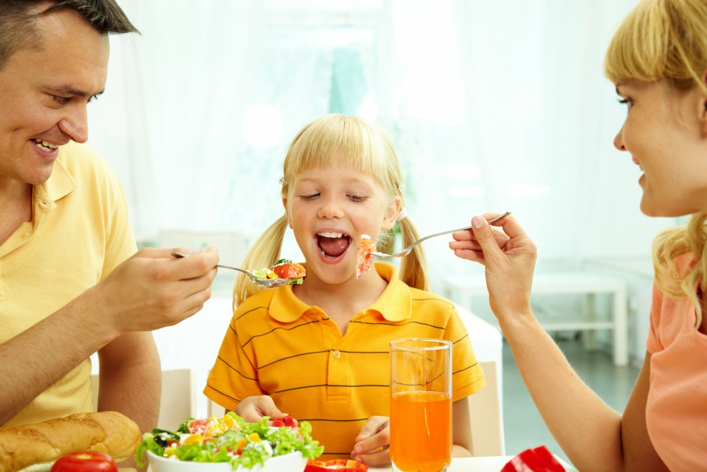 parents feeding their daughter with salad in the kitchen
